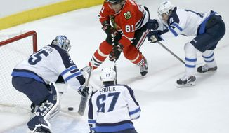 Winnipeg Jets goalie Al Montoya (35) makes a save on a shot by Chicago Blackhawks right wing Marian Hossa (81) as Michael Frolik (67) and James Wright defend during the first period of an NHL hockey game Sunday, Jan. 26, 2014, in Chicago. (AP Photo/Charles Rex Arbogast)