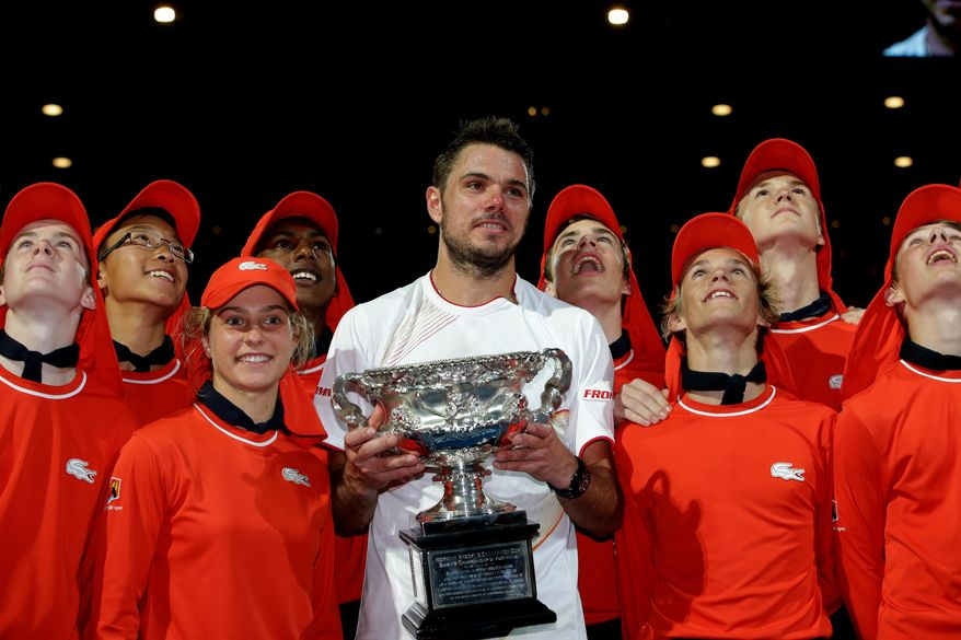 Stanislas Wawrinka of Switzerland poses with the trophy, along with ball boys and girls,  after defeating Rafael Nadal of Spain in the men's singles final at the Australian Open tennis championship in Melbourne, Australia, Sunday, Jan. 26, 2014. (AP Photo/Aaron Favila)