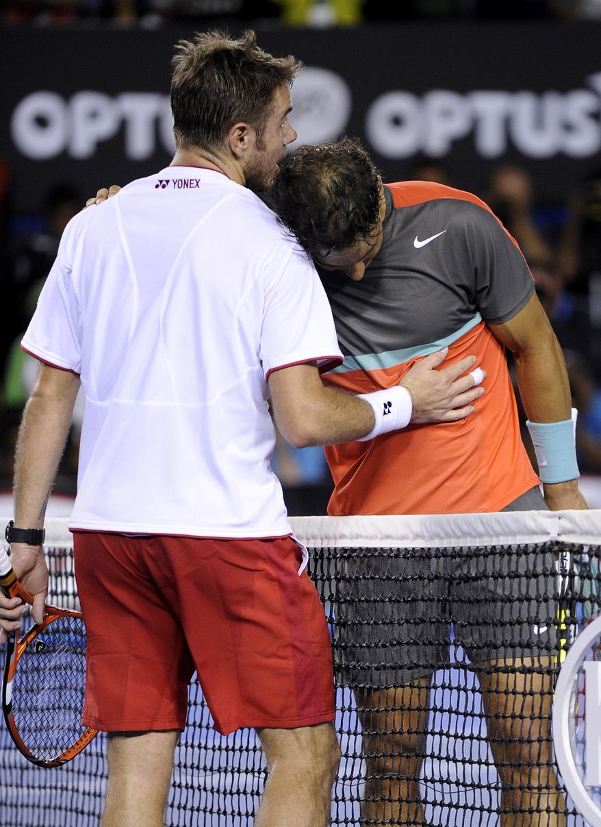 Stanislas Wawrinka of Switzerland, left, talks with Rafael Nadal of Spain at the net after Wawrinka won the men's singles final at the Australian Open tennis championship in Melbourne, Australia, Sunday, Jan. 26, 2014. (AP Photo/Andrew Brownbill)