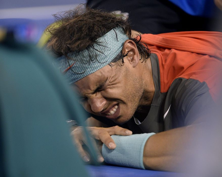 Rafael Nadal of Spain grimaces as he receives a medical treatment to his back in the men's singles final against Stanislas Wawrinka of Switzerland at the Australian Open tennis championship in Melbourne, Australia, Sunday, Jan. 26, 2014.(AP Photo/Andrew Brownbill)