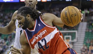 Washington Wizards' Nene (42) drives to the basket as Utah Jazz's Derrick Favors, rear, defends during the second quarter of an NBA basketball game Saturday, Jan. 25, 2014, in Salt Lake City. (AP Photo/Rick Bowmer)