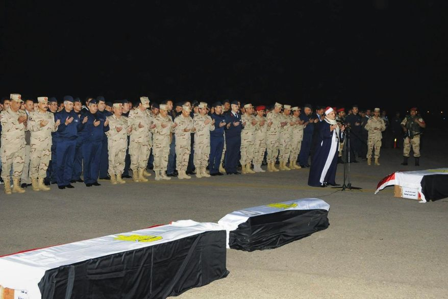 In this undated photo released by the Egyptian Defense Ministry, officers and soldiers pray during a funeral for several military personnel who were killed when a helicopter crashed in the Sinai Peninsula, at an undisclosed location in Egypt. Egypt's military spokesman, Col. Ahmed Mohammed Ali said that an Air Force helicopter crashed near the village of el-Kharouba in the northern Sinai Peninsula early Saturday, where troops are battling Islamic militants. An al-Qaida-inspired group based in the Sinai Peninsula has claimed responsibility for bringing down an Egyptian military helicopter in the lawless desert region. (AP Photo/Egyptian Defense Ministry via Facebook)