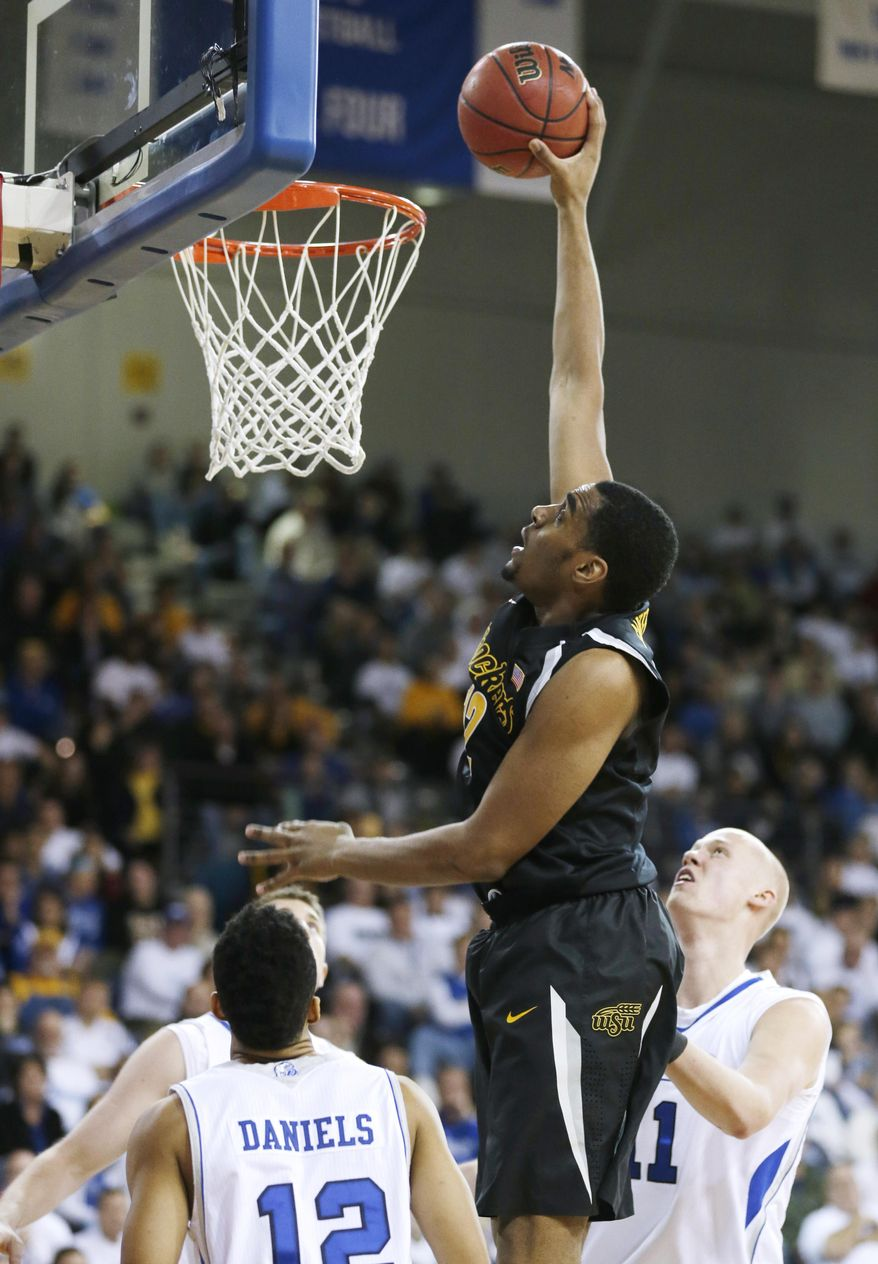 Wichita State forward Darius Carter, center, looks to dunk the ball over Drake guard Jordan Daniels, left, and Jacob Enevold, right, during the second half of an NCAA college basketball game, Saturday, Jan. 25, 2014, in Des Moines, Iowa. Wichita State won 78-61. (AP Photo/Charlie Neibergall)