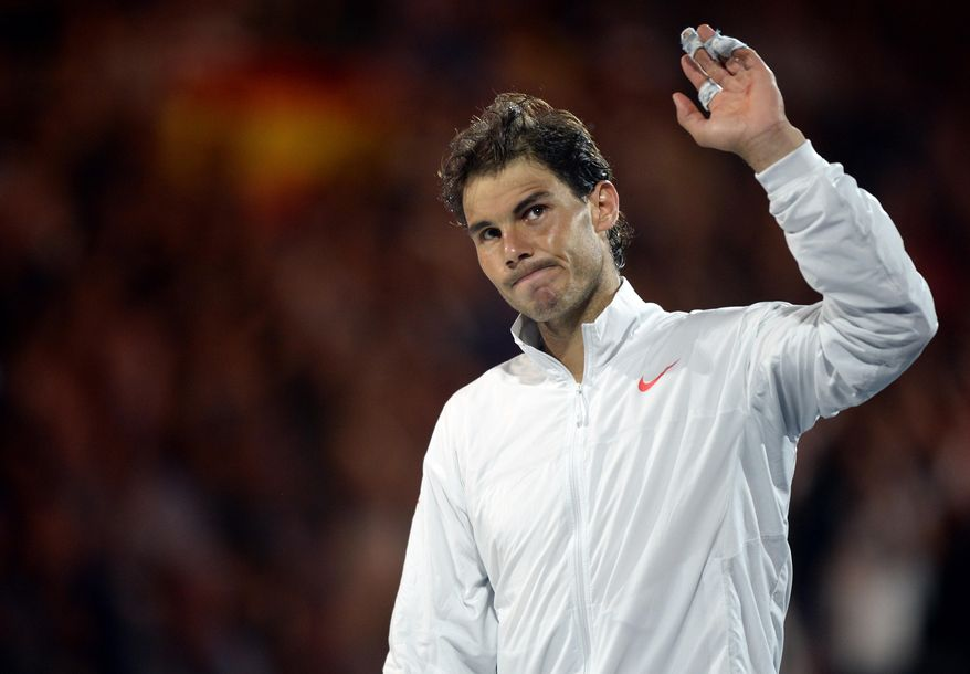 Rafael Nadal of Spain waves to the spectators during the trophy presentation after his loss to Stanislas Wawrinka of Switzerland in the men's singles final at the Australian Open tennis championship in Melbourne, Australia, Sunday, Jan. 26, 2014. (AP Photo/Andrew Brownbill)
