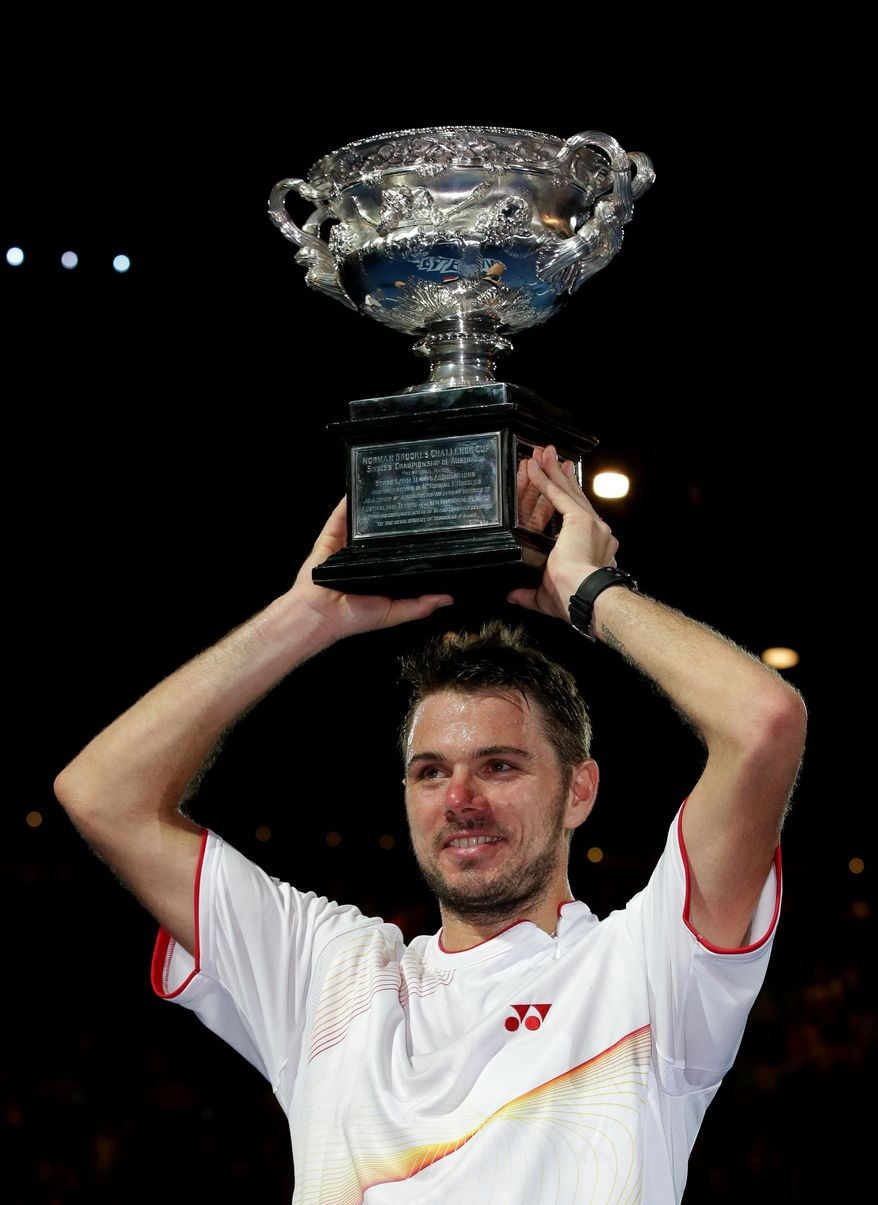 Stanislas Wawrinka of Switzerland holds up  the trophy after defeating Rafael Nadal of Spain in the men's singles final at the Australian Open tennis championship in Melbourne, Australia, Sunday, Jan. 26, 2014. (AP Photo/Aaron Favila)