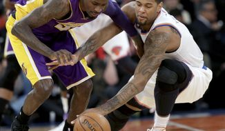 Los Angeles Lakers' Manny Harris, left, and New York Knicks' Jeremy Tyler fight for the ball during the second half of an NBA basketball game at Madison Square Garden Sunday, Jan. 26, 2014, in New York. The Knicks won 110-103. (AP Photo/Seth Wenig)