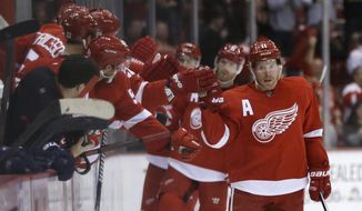 Detroit Red Wings right wing Daniel Alfredsson, right, of Sweden, is congratulated by teammates after scoring during the second period of an NHL hockey game against the Florida Panthers in Detroit, Sunday, Jan. 26, 2014. (AP Photo/Carlos Osorio)