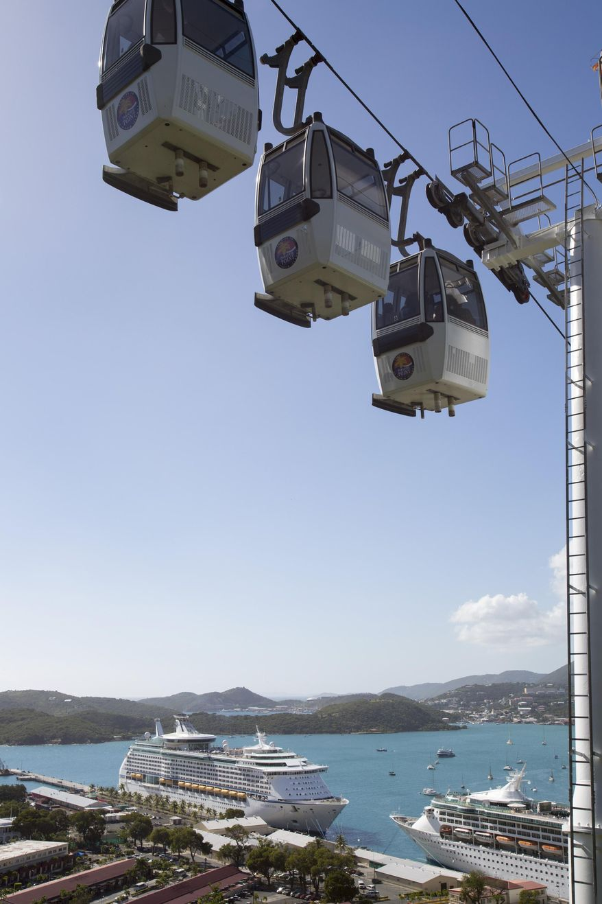 The Royal Caribbean International's Explorer of the Seas crusie ship, bottom left, is docked at Charlotte Amalie Harbor in St. Thomas, U. S. Virgin Islands, Sunday, Jan. 26, 2014. U.S. health officials have boarded the cruise ship to investigate an illness outbreak that has stricken at least 300 people with gastrointestinal symptoms including vomiting and diarrhea. (AP Photo/Thomas Layer)