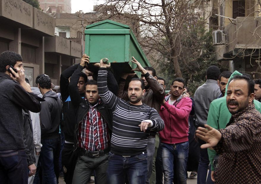Egyptians carry the coffin of a man killed during Saturday's clashes between protesters and security forces near the Zeinhom morgue in Cairo, Egypt, Sunday, Jan. 26, 2014. Egyptian officials said Sunday that the death toll from clashes between security forces and protesters on the third anniversary of the country's 2011 uprising has risen to 49. (AP Photo/Aly Hazzaa, El Shorouk) EGYPT OUT