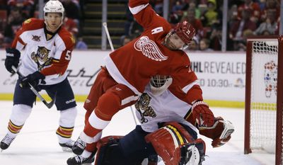 Detroit Red Wings right wing Daniel Cleary (71) falls over Florida Panthers goalie Tim Thomas (34) during the first period of an NHL hockey game in Detroit, Sunday, Jan. 26, 2014. (AP Photo/Carlos Osorio)
