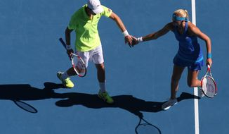 Kristina Mladenovic of France and Daniel Nestor of Canada celebrate a point won against Sania Mirza of India Horia Tecau of Romania during the mixed doubles final at the Australian Open tennis championship in Melbourne, Australia, Sunday, Jan. 26, 2014.(AP Photo/Eugene Hoshiko)