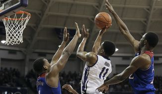 TCU forward Brandon Parrish (11) attempts a shot as Kansas' Wayne Selden Jr. (1) and Andrew Wiggins (22) defend in the second half of an NCAA college basketball game, Saturday, Jan. 25, 2014, in Fort Worth, Texas. Kansas won 91-69. (AP Photo/Brandon Wade)