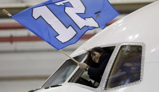 Delta flight attendant Christi Turner waves a flag as the charter plane carrying the Seattle Seahawks arrives at Newark Liberty International Airport for the NFL Super Bowl XLVIII football game, Sunday, Jan. 26, 2014, in Newark, N.J. (AP Photo/Julio Cortez)