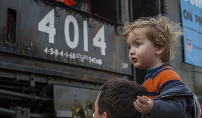Kirk Hofstetter, of Fullerton, carries his son Theodore, 1, to view the historic locomotive, Union Pacific Big Boy No. 4014 at Metrolink Station, Sunday, Jan. 26, 2014, in Covina, Calif. (AP Photo/Ringo H.W. Chiu)