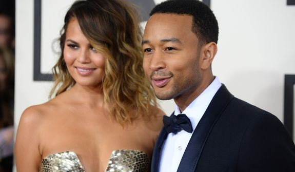Christine Teigen, left, and John Legend arrive at the 56th annual GRAMMY Awards at Staples Center on Sunday, Jan. 26, 2014, in Los Angeles. (Photo by Jordan Strauss/Invision/AP)