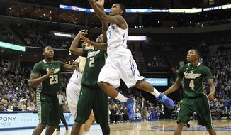 Memphis guard Joe Jackson (1) drives to the basket against USF defenders Chris Perry (23), Victor Rudd (2) and Corey Allen, Jr. (4) in the first half of an NCAA college basketball game Sunday, Jan. 26, 2014, in Memphis, Tenn. (AP Photo/Lance Murphey)