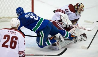 Vancouver Canucks' Kevin Bieksa, centre, scores the winning goal against Phoenix Coyotes' goalie Mike Smith, right, as Michael Stone watches during an NHL hockey game in Vancouver, British Columbia, on Sunday, Jan. 26, 2014. (AP Photo/The Canadian Press, Darryl Dyck)