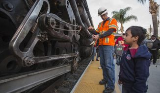 Miguel Angel Warner, right, 4, of Los Angeles, asks Ed Dickens, left, senior manager of  Heritage Operations about the historic locomotive, Union Pacific Big Boy No. 4014 at Metrolink Station, Sunday, Jan. 26, 2014, in Covina, Calif. The locomotive will head for Colton over the next several weeks before No. 4014 departs for Union Pacific's Heritage Fleet Operations headquarters in Cheyenne, Wyo. (AP Photo/Ringo H.W. Chiu)