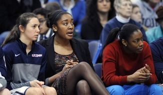 Briana Pulido, Morgan Tuck and Brianna Banks, left to right, watch action during the second half of Connecticut's 81-53 victory over South Florida in an NCAA college basketball game in Hartford, Conn., Sunday, Jan. 26, 2014. (AP Photo/Fred Beckham)