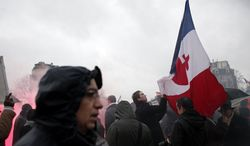 """A protestor holds a French flag during a demonstration to criticize President Francois Hollande, in Paris, Sunday, Jan. 26, 2014. Carrying banners saying """"The French are angry!"""" Sunday's demonstration by people from about 50 organizations cited France's struggling economy and high unemployment, its taxes, their housing needs and lack of personal freedoms. Placard reading """"Freedom of speech"""". (AP Photo/Thibault Camus)"""