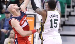 Utah Jazz's Derrick Favors (15) shoots as Washington Wizards' Marcin Gortat (4), of Poland, defends in the second half during an NBA basketball game Saturday, Jan. 25, 2014, in Salt Lake City. The Jazz won 104-101. (AP Photo/Rick Bowmer)