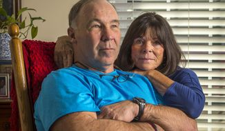 In this Jan. 23, 2014 photo, Pro Football Hall of Famer Joe DeLamielleure poses with his wife Gerri in their home in Charlotte, N.C. DeLamielleure is convinced that he, like many former professional football players, suffers from a concussion-related brain disease CTE brought on by the many head blows and concussions experienced during his 13 year NFL career. (AP Photo/Bob Leverone)