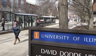 Students walk between buildings and wait for buses on the University of Illinois campus in Urbana, Ill., on Monday, Jan. 27, 2014. The university decided to conduct classes despite bitter cold weather that left wind chills well below zero. Some other Illinois universities held classes Monday, too, but a few told students to stay home.  (AP Photo/David Mercer)