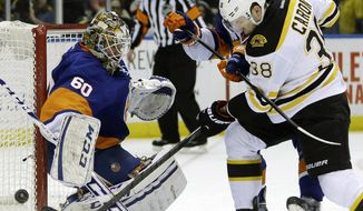 Boston Bruins' Jordan Caron, right, and New York Islanders' Calvin de Haan scuffle for the puck in front of goalie Kevin Poulin, left,  during the first period of the NHL hockey game, Monday, Jan. 27, 2014, in Uniondale, New York. (AP Photo/Seth Wenig)