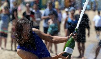 China's Li Na sprays champagne as she poses for photos at Brighton Beach with her Australian Open trophy following her win over Slovakia's Dominika Cibulkova in Melbourne, Australia, Sunday, Jan. 26, 2014. (AP Photo/Rick Rycroft)