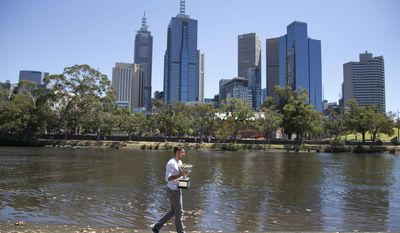 Switzerland's Stanislas Wawrinka poses with his Australian Open trophy on the banks of the Yarra River following his win over Spain's Rafael Nadal on Sunday evening in Melbourne, Australia, Monday, Jan. 27, 2014. (AP Photo/Mark Baker)