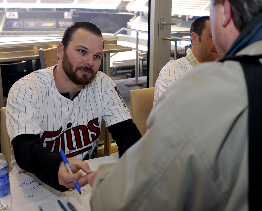 Minnesota Twins' Jason Kubel signs an autograph for a fan during the baseball team's TwinsFest at Target Field on Friday, Jan. 24, 2014, in Minneapolis. (AP Photo/Hannah Foslien)