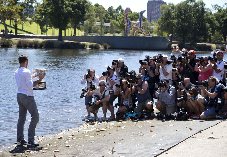 Switzerland's Stanislas Wawrinka poses for photographers with his Australian Open trophy on the banks of the Yarra River following his win over Spain's Rafael Nadal on Sunday evening in Melbourne, Australia, Monday, Jan. 27, 2014. (AP Photo/Mark Baker)