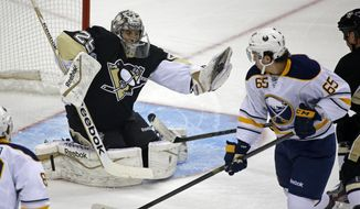 Pittsburgh Penguins goalie Marc-Andre Fleury (29) makes a glove save on a shot by Buffalo Sabres' Brian Flynn (65) during the first period of an NHL hockey game between the Pittsburgh Penguins and the Buffalo Sabres in Pittsburgh, Monday, Jan. 27, 2014. The Penguins won 3-0. (AP Photo/Gene J. Puskar)