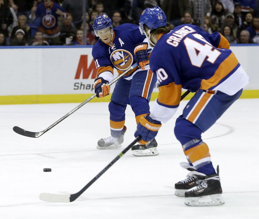 New York Islanders' Kyle Okposo, left, passes to Michael Grabner before scoring during the second period of the NHL hockey game against the Boston Bruins, Monday, Jan. 27, 2014, in Uniondale, New York. (AP Photo/Seth Wenig)