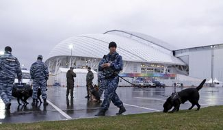 Security personnel walk with their dogs outside Fisht Olympic Stadium at the 2014 Winter Olympics Monday, Jan. 27, 2014, in Sochi, Russia. The Olympics begin Feb. 7th. (AP Photo/David J. Phillip)