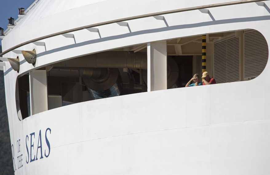 Passengers look out from the Royal Caribbean International's Explorer of the Seas, docked at Charlotte Amalie Harbor in St. Thomas, U. S. Virgin Islands, Sunday, Jan. 26, 2014. U.S. health officials have boarded the cruise ship to investigate an illness outbreak that has stricken at least 300 people with gastrointestinal symptoms including vomiting and diarrhea. (AP Photo/Thomas Layer)