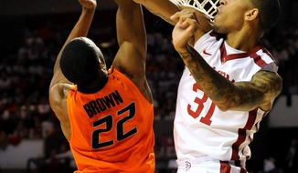 Oklahoma forward D.J. Bennett (31), blocks a shot by Oklahoma State guard Markel Brown during the first half of an NCAA college basketball game in Norman, Okla., Monday, Jan. 27, 2014. (AP Photo/Brody Schmidt)