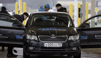 Russian police officers search a vehicle at an entrance to the Sochi 2014 Olympic Winter Games park, Thursday, Jan. 23, 2014, in Sochi, Russia. The Olympics begin on Feb. 7. (AP Photo/David J. Phillip)