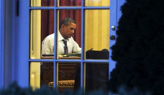 As seen from the Rose Garden, President Barack Obama works at his desk in the Oval Office of the White House in Washington, Monday, Jan. 27, 2014, ahead of Tuesday night's State of the Union speech. (AP Photo/Jacquelyn Martin)