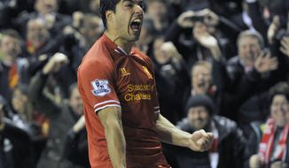 Liverpool's Luis Suarez celebrates after he scores the fourth goal of the game for his side during their English Premier League soccer match against Everton at Anfield in Liverpool, England, Tuesday Jan. 28, 2014. (AP Photo/Clint Hughes)