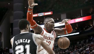 San Antonio Spurs' Tim Duncan (21) knocks the ball away from Houston Rockets' Dwight Howard (12) during the first half of an NBA basketball game Tuesday, Jan. 28, 2014, in Houston. (AP Photo/Pat Sullivan)
