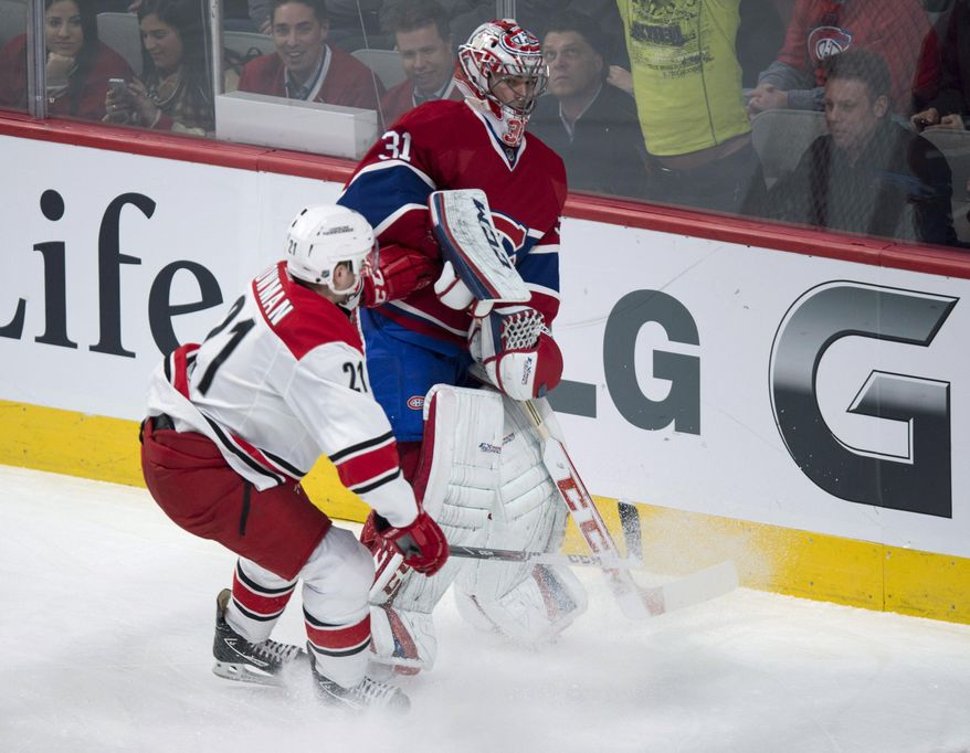 Carolina Hurricanes' Drayson Bowman bumps up against Montreal Canadiens goalie Carey Price as Price clears the puck from behind the net during the first period of an NHL hockey game Tuesday, Jan. 28, 2014, in Montreal. (AP Photo/The Canadian Press, Paul Chiasson)
