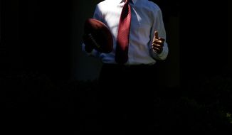 President Barack Obama stands in a shaft of light while playing football outside the Oval Office May 20, 2009.  (Official White House photo by Pete Souza.)