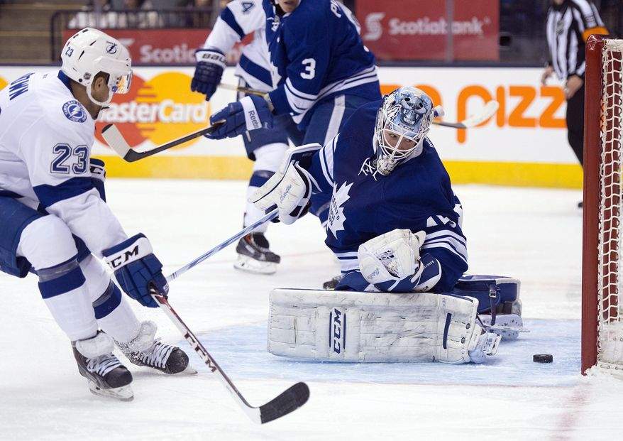 Toronto Maple Leafs goaltender Jonathan Bernier, right, makes a save on Tampa Bay Lightning right winger J.T. Brown (23) during first period of an NHL game in Toronto, Tuesday, Jan. 28, 2014. (AP Photo/The Canadian Press, Frank Gunn)