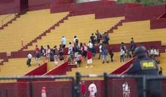 Students are moved to an on-campus stadium at Roosevelt High School after a school shooting, Tuesday, Jan. 28, 2014, in Honolulu. A 17-year-old student was shot by police in a counselor's office after he pulled a knife and cut one of the officers.  The student was taken to a local hospital. State Department of Education spokeswoman Donalyn Dela Cruz said the boy showed up Tuesday morning at the school and officials there recognized him as a runaway who was not registered for classes, and called police. (AP Photo/Marco Garcia)
