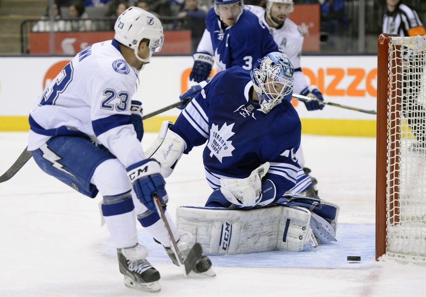 Toronto Maple Leafs goalie Jonathan Bernier, center, makes a save as Tampa Bay Lightning's J.T. Brown (23) looks for a rebound during first period of an NHL game in Toronto, Tuesday, Jan. 28, 2014. (AP Photo/The Canadian Press, Frank Gunn)