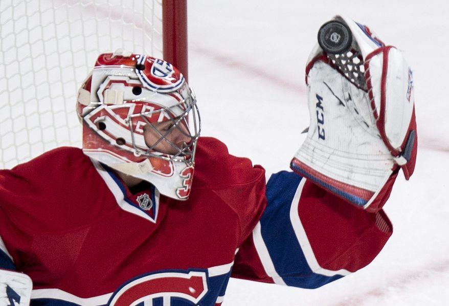 Montreal Canadiens goalie Carey Price makes a glove save during the second period of an NHL hockey game against the Carolina Hurricanes, Tuesday, Jan. 28, 2014, in Montreal. (AP Photo/The Canadian Press, Paul Chiasson)