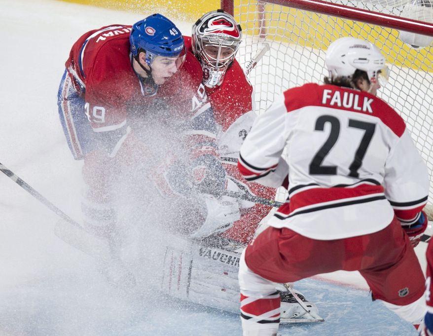 Montreal Canadiens' Michael Bourniva collides with Carolina Hurricanes goalie Anton Khudobin as Justin Faulk watches during the second period of an NHL hockey game Tuesday, Jan. 28, 2014, in Montreal. (AP Photo/The Canadian Press, Paul Chiasson)