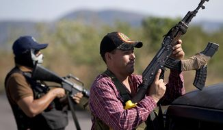FILE - In this Jan. 14, 2014 file photo, armed men belonging to the Self-Defense Council of Michoacan, (CAM), stand guard at a checkpoint at the entrance of Antunez, Mexico. The government announced that it had reached a deal with vigilante leaders to incorporate the armed civilian groups into old and largely forgotten quasi-military units called the Rural Defense Corps. Vigilante leaders met Tuesday Jan. 28, with government officials to hash out details of the agreement. (AP Photo/Eduardo Verdugo, file)