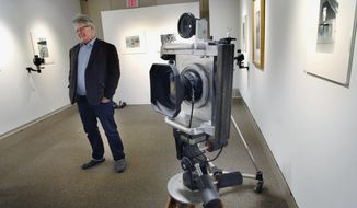 "In this Jan. 10, 2014 photo, Bloomington artist Kevin Strandberg, a professor of art at Illinois Wesleyan University, poses at the McLean County Art Center in Bloomington, Ill., where he has adapted several older film cameras to make a variety of unique images in his exhibit, ""The Franken-Camera Project."" In the foreground is a drastically modified Polaroid copy camera, complete with a viewfinder made from a Moto Guzzi motorcycle fork. (AP Photo/The Pantagraph, David Proeber)"
